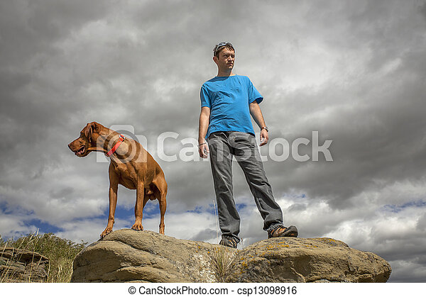 man and dog on top of cliff - csp13098916
