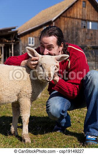 Man and lamb and a farmhouse - csp19149227