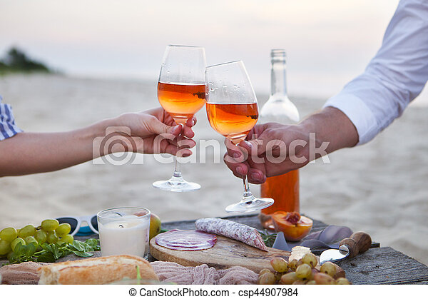 Man and woman clanging wine glasses with rose wine at sunset beach - csp44907984