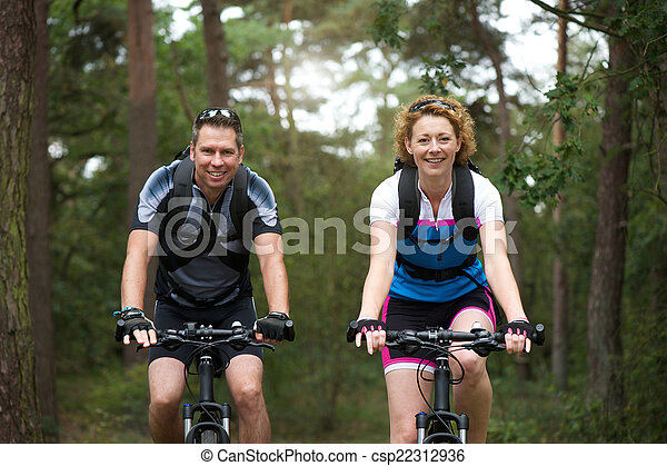 Man and woman cyclist smiling outdoors  - csp22312936