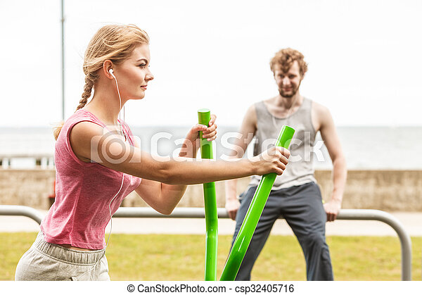 Man and woman exercising on elliptical trainer. - csp32405716