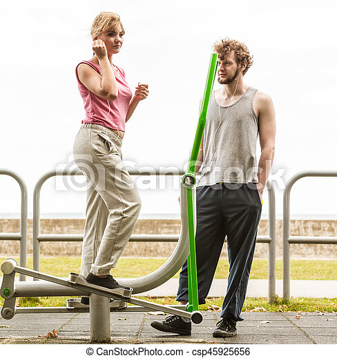 Man and woman exercising on elliptical trainer. - csp45925656