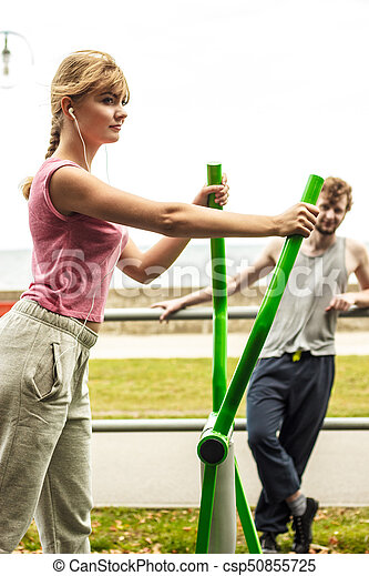 Man and woman exercising on elliptical trainer. - csp50855725