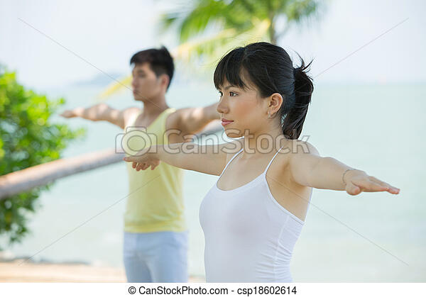 Man and Woman performing yoga. - csp18602614
