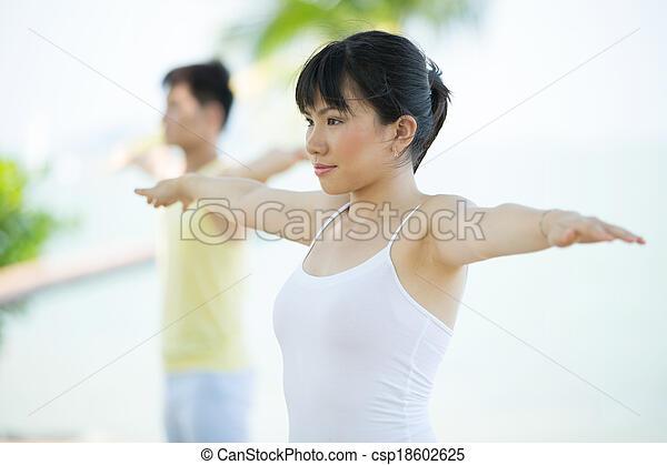 Man and Woman performing yoga. - csp18602625