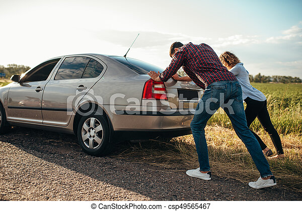 man and woman pushing a broken car back view man and woman pushing