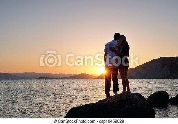 Man and woman standing in an embrace and watch the sunset - csp10459029