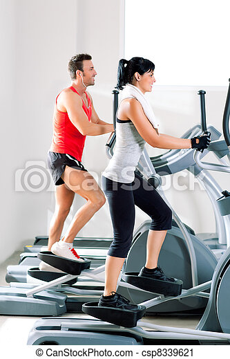 man and woman with elliptical cross trainer at gym - csp8339621