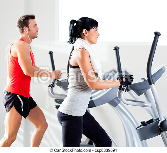 man and woman with elliptical cross trainer at gym - csp8339691