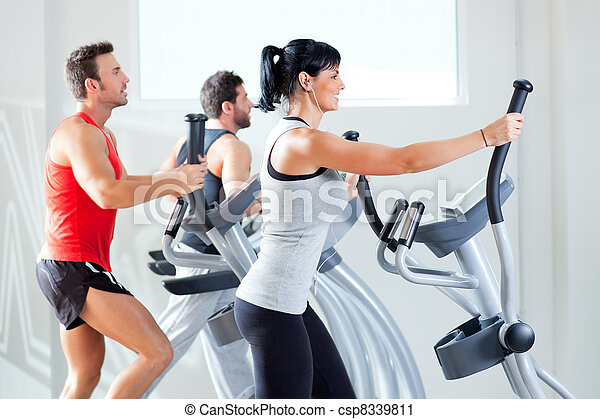 man and woman with elliptical cross trainer at gym - csp8339811