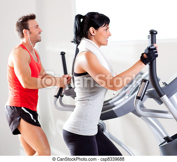 man and woman with elliptical cross trainer at gym - csp8339688