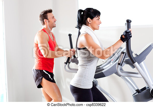 man and woman with elliptical cross trainer at gym - csp8339622