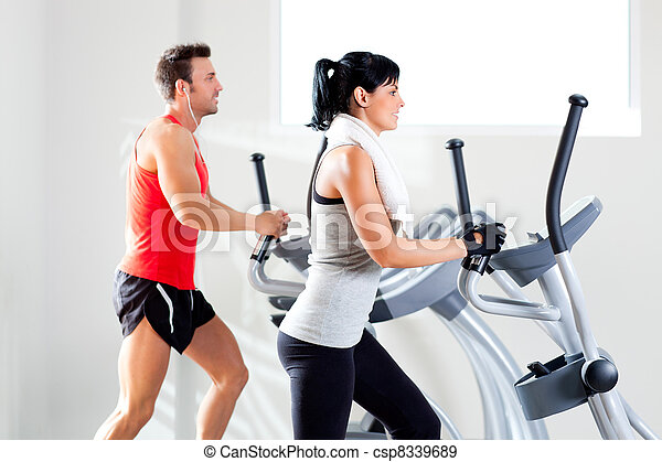 man and woman with elliptical cross trainer at gym - csp8339689
