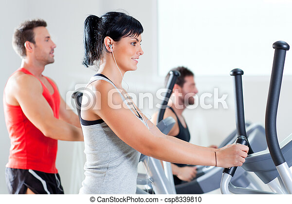 man and woman with elliptical cross trainer at gym - csp8339810