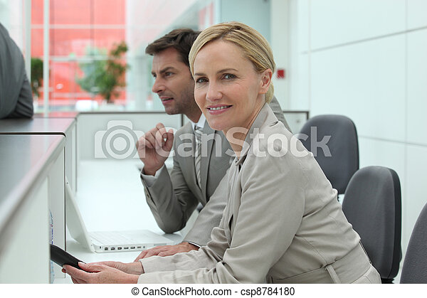 Man and woman working behind a reception desk - csp8784180