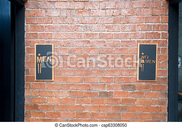 Man and women signs on public restroom on brick wall - csp63308050