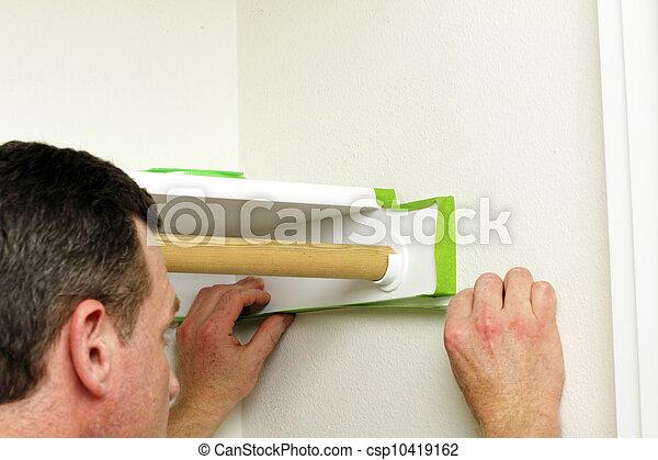 Man Applying Green Painter's Tape - csp10419162