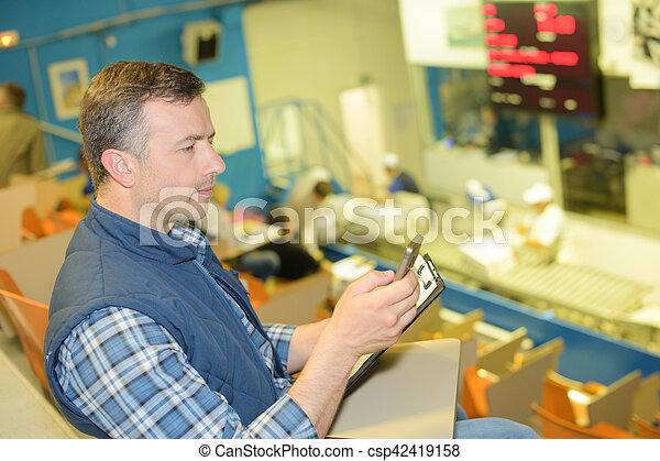 Man at market using mobile phone - csp42419158