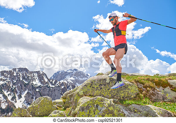 Man athlete jumps between the stones during a trail workout in the mountains - csp92521301