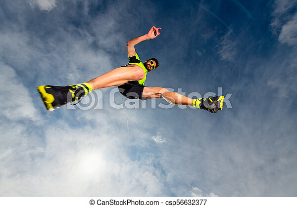 Man athlete while jumping during a trail running in the mountains - csp56632377