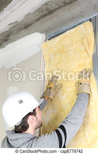 Man attaching insulation to wall - csp8779742