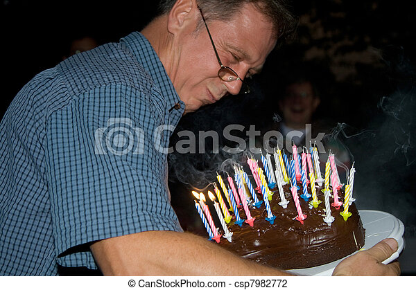 man blows out his birthday candles at the birthday - csp7982772