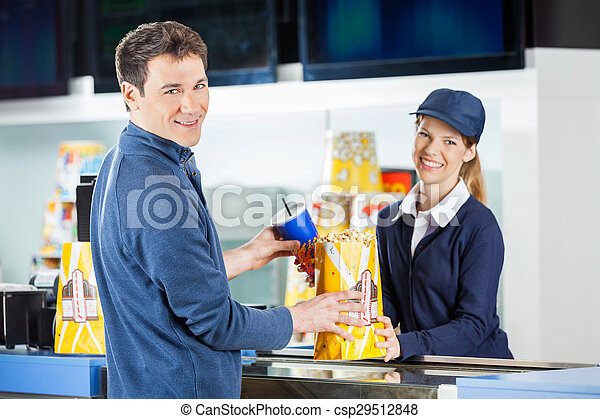 Man buying popcorn and drink from seller at concession... stock ...