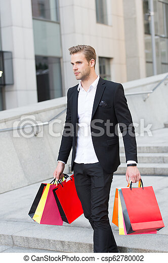 Man carry shopping bags on urban backdrop. Businessman with package walk in street. Fashion shopper with paperbags. Great day for shopping. Big sale on black friday. Man bought many birthday presents. - csp62780002