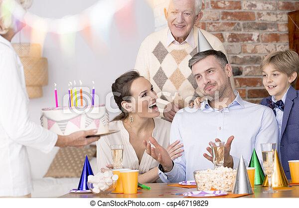 Man celebrating birthday with family, senior woman holding cake