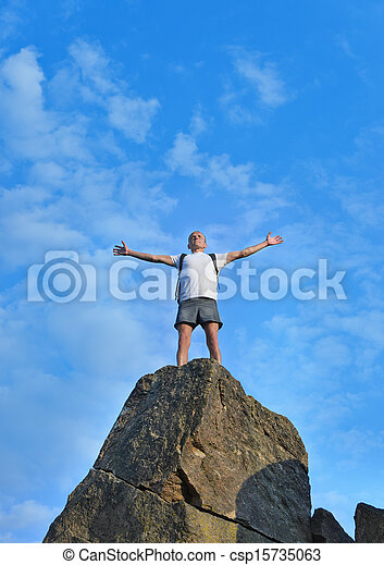 Man celebrating reaching the top of a mountain - csp15735063
