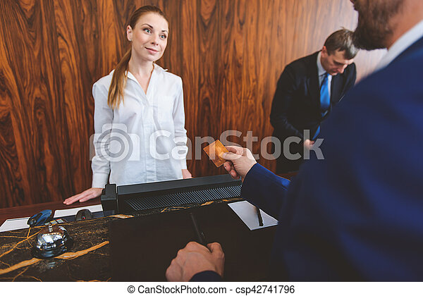 Man checking in at reception desk - csp42741796