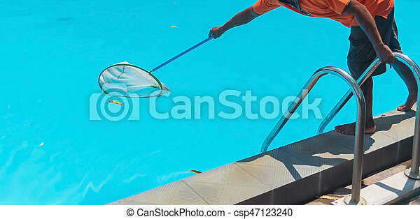 Man cleaning the blue swimming pool from leaves with cleaning net.
