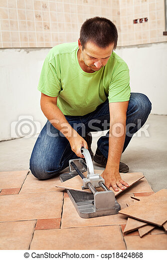 Man Cutting Ceramic Floor Tiles Installing Them In A New Building