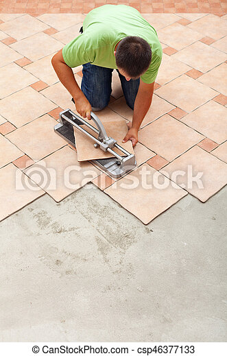 Man Cutting Ceramic Floor Tiles With Manual Cutter Knealing On The