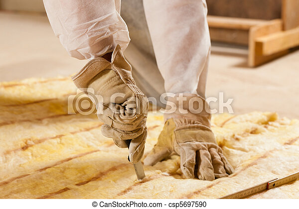 Man cutting insulation material for building - csp5697590