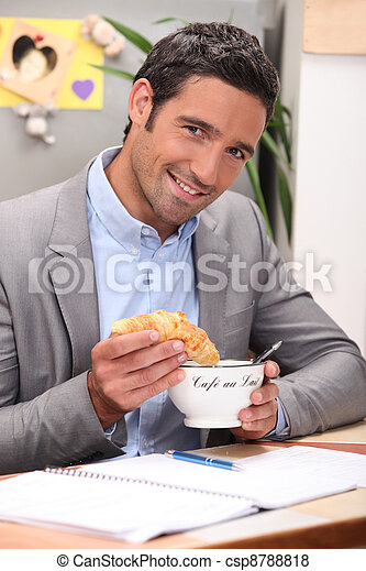 Man dipping croissant into coffee - csp8788818