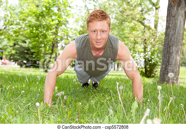 Man doing a push up in park - csp5572808