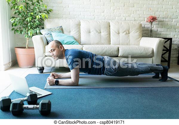 Man doing workout routine found online - csp80419171