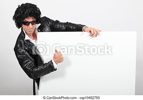 Man dressed as Elvis holding message board - csp10452750
