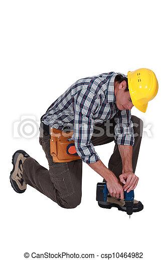 Man drilling hole in floor - csp10464982