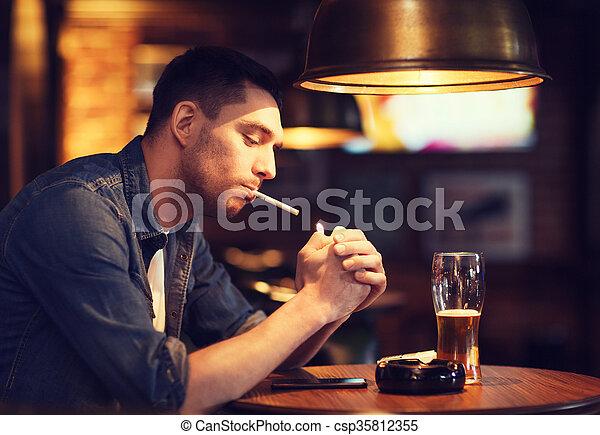 Man Drinking Beer And Smoking Cigarette At Bar People