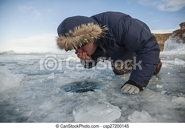 Man drinking water from a hand hole of lake