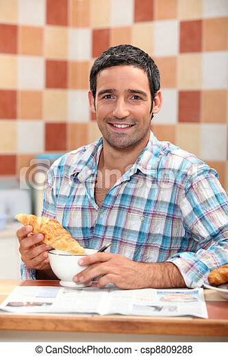 Man dunking a croissant into a cafe au lait at breakfast time - csp8809288