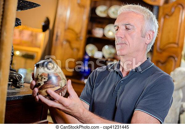 Man examining an antique pot - csp41231445
