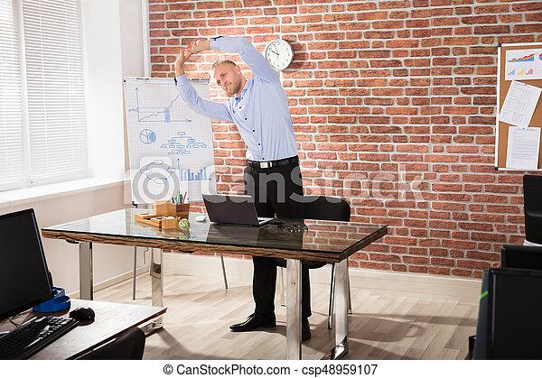 Happy Businessman Exercising During Break In Modern Office