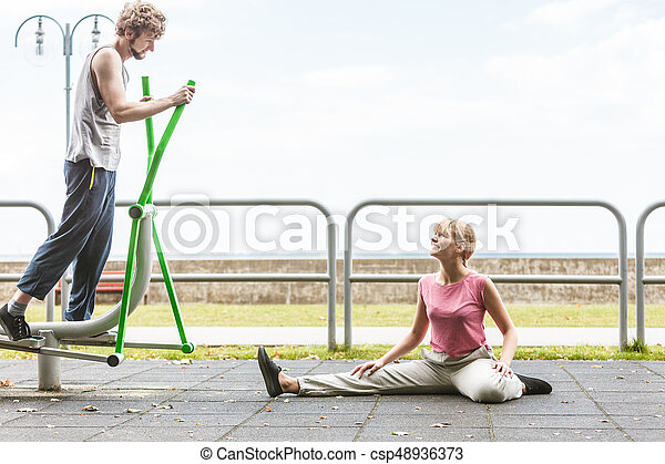 Man exercising on elliptical trainer and woman. - csp48936373