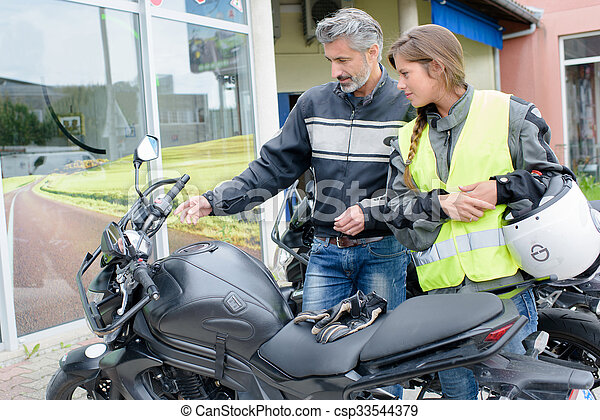 Man explaining controls of a motorcycle to a lady - csp33544379