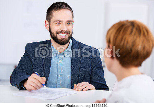 Man Explaining Documents To Female Co worker At Desk - csp14448440