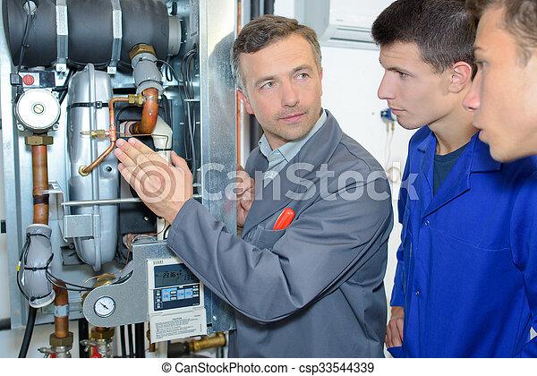 Man explaining machinery to trainees - csp33544339