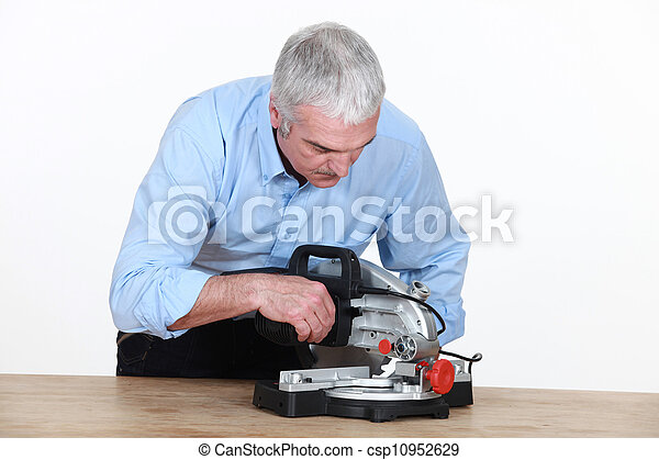 Man figuring out how to operate his new mitre saw - csp10952629